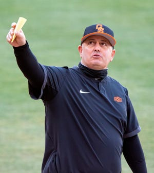 Oklahoma State coach Josh Holliday points to the stands as he talks to the umpire during a game on Feb. 24 in Stillwater.