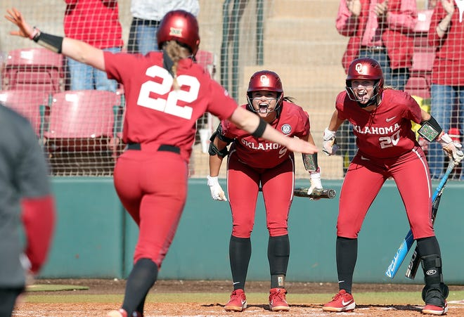 OU's Taylon Snow (5) and Jana Johns (20) greet Lynnsie Elam (22) after Elam's solo home run Sunday in the Sooners' 9-0 win over Texas on Sunday in Norman.