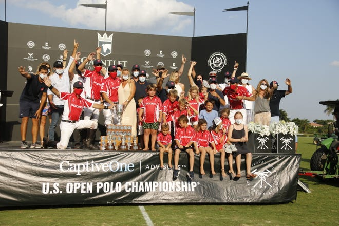 The players of the winning Scone team, as well as families and friends, celebrate their victory in the CaptiveOne U.S. Open Polo Championship Sunday at International Polo Club Palm Beach.