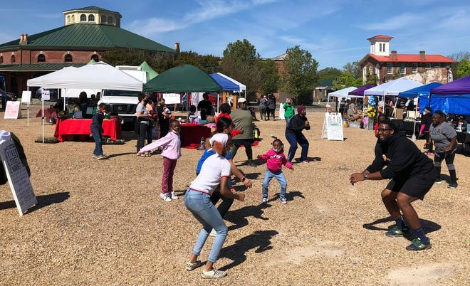 "Front right, Markus Copeland with Self Dreams LLC provides free HIIT [High Intensity Interval Training] at River Street Market's  ""Get Fit Petersburg Market"" in Old Towne Petersburg on April 17, 2021."