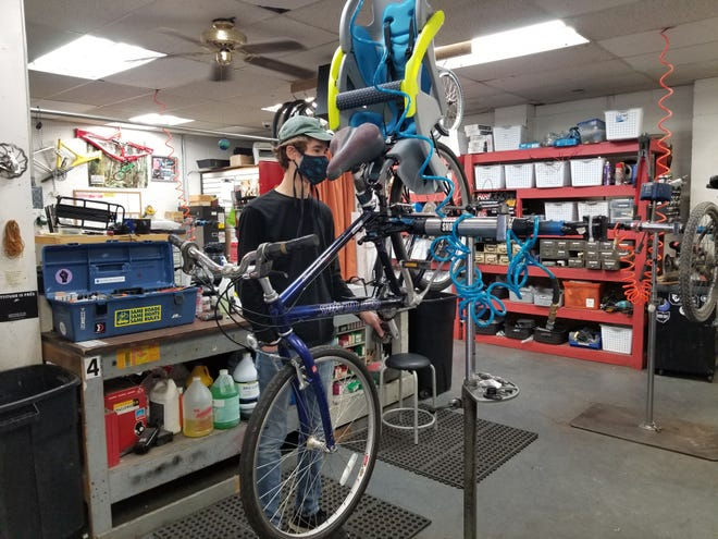 Chase Caughey, an employee at Ernie's Bicycle Shop, looks at repair work needed on a customer's bike. Store employees say bikes are harder to come by due to the pandemic and so are the parts needed to fix them. (Lori Steineck / The Canton Repository)