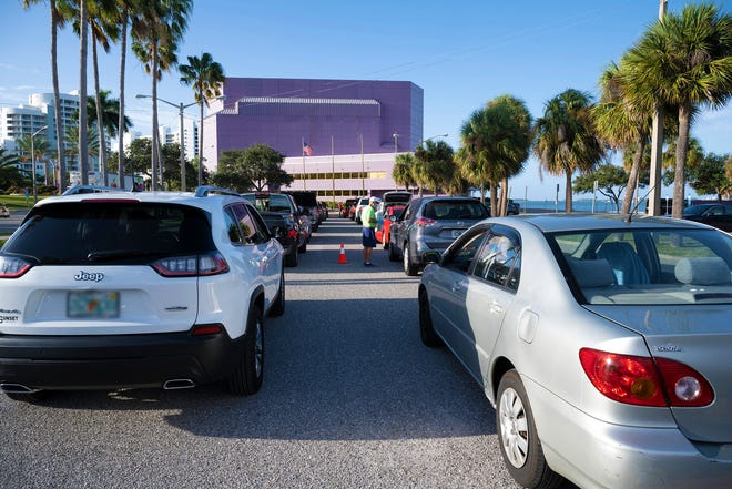 Hundreds of community members received Thanksgiving dinners and bouquets of flowers in 2020 during an All Faiths Food Bank distribution at Van Wezel Performing Arts Hall in Sarasota.