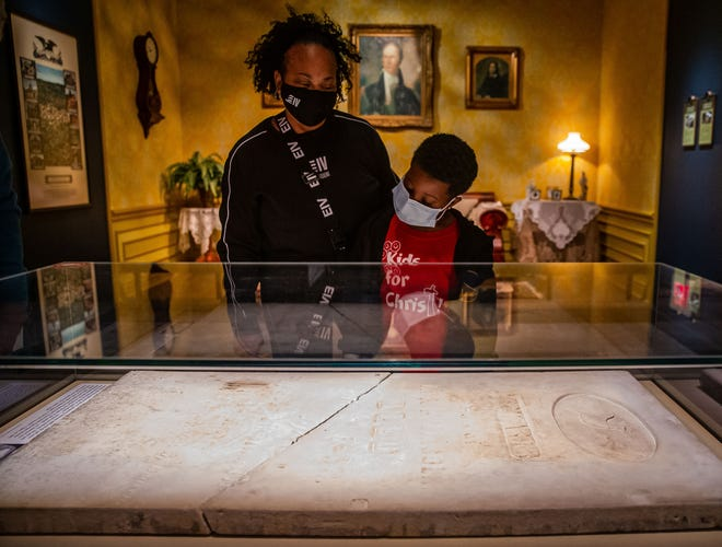 """Eddie Snow IV looks over the tombstone of Edward Baker """"Eddie"""" Lincoln while going through the Abraham Lincoln Presidential Museum with his grandmother, Valeria Senor, on the 16th anniversary of the ALPM in Springfield, Ill., Monday, April 19, 2021.  [Justin L. Fowler/The State Journal-Register]"""