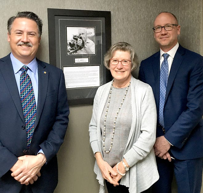 Jane Odom, center, poses with a sample of her father's work, along with Eric Eishen, president of Sturgis Bank & Trust, and Vince Little, president of Oakleaf Financial Services.