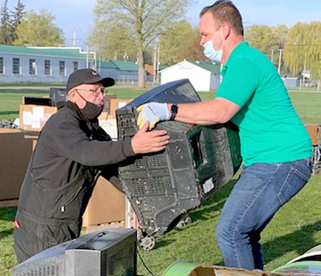 Employees from Green Earth Electronics Recycling handle one of hundreds of televisions taken to an electronics-recycling event Saturday at the St. Joseph County fairgrounds in Centreville.