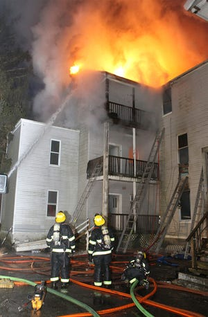 Firefighters work at the back of 7 Lowell St. on the morning of Dec. 9, 2018.