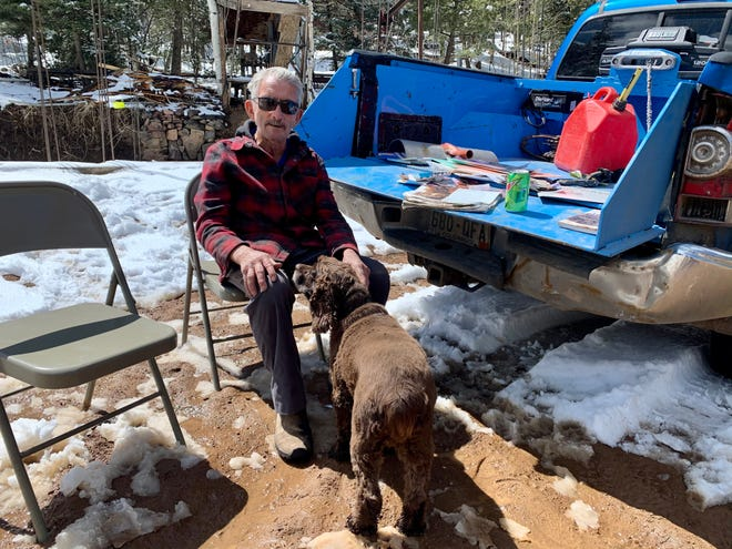 Jim Bishop and his dog Marley sit on the Bishop Castle property on April 18, 2021.