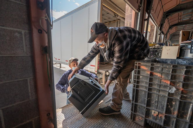 Jack Pendleton, left, hands a television to Wesley McCormick before weighing it at 3R Technology Solutions on Monday April 19, 2021.
