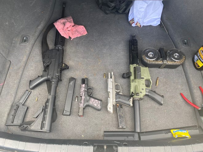 Guns were seized and three men were charged with marijuana possession after reports of machine-gun fire at McKenzie Court on Sunday.