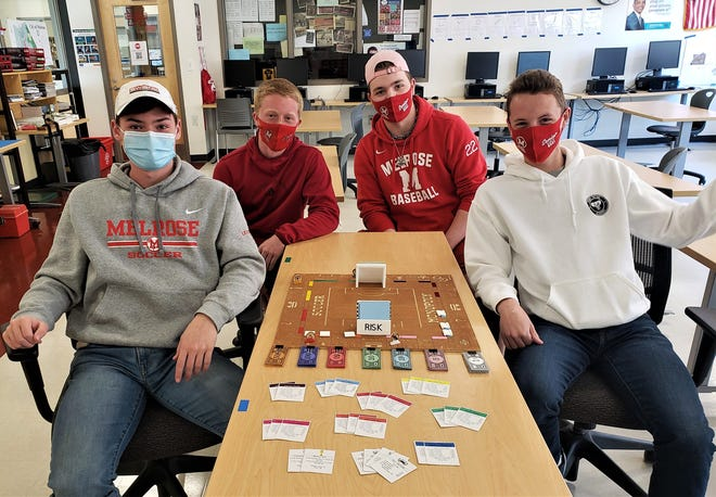 John LeComte, Jacobus Overgaag, Eric McGovern and Cam McDonough with the FIFA Monopoly game they designed and built in their Advanced CAD class at Melrose High School. Grants from the Melrose Education Foundation helped fund the technology tools and equipment they used to complete the project.