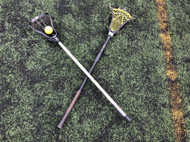Two lacrosse sticks sit on the ground at Count Basie Field in Red Bank during the Red Bank Catholic girls lacrosse game versus Manasquan on April 19, 2021.