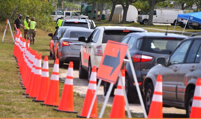 Motorists line up for drive-through COVID-19 vaccinations outside the Florida Department of Health complex in Viera.