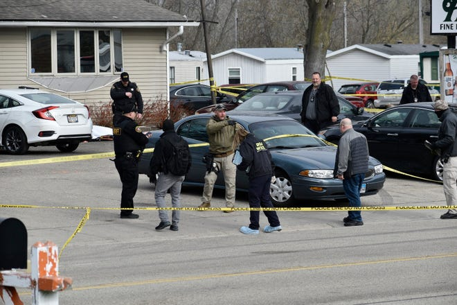 Investigators confer during an investigation outside the Somers House Tavern, in Kenosha, Wis., Sunday morning, April 18, 2021.