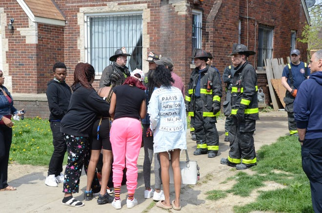 Neighbors, friends and family gather along with Detroit firefighters at the scene of a house fire on Camden Street in Detroit Monday afternoon, April 19, 2021.