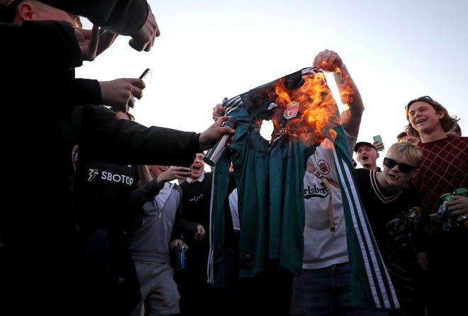 Fans burn a Liverpool replica shirt outside Elland Road, as a protest against Liverpool's decision to be included amongst the clubs attempting to form a new European Super League, in Leeds, England, Monday, April 19, 2021.