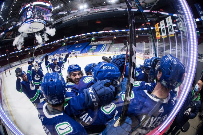 Vancouver Canucks' Bo Horvat is mobbed by teammates after scoring the winning goal during overtime.