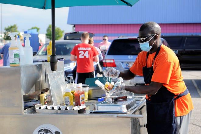 Emmanuel Adiki dishes up a hot dog at his Hot Diggity Dog (Just Doggin' Around) cart on Saturday, April 17, 2021.