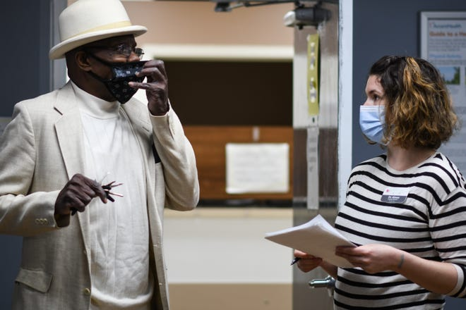 Dr. Aimee Leisure-Martins of the Cristo Rey Community Health Center reviews pre-screening questions with Paul Harvell, 74, of Lansing Monday.
