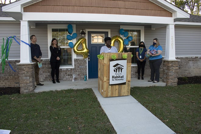 Pensacola Habitat for Humanity celebrates its 40th anniversary with 1,400th home dedication. The 1,400th homebuyer, Toccora Ervin, stands behind a podium.