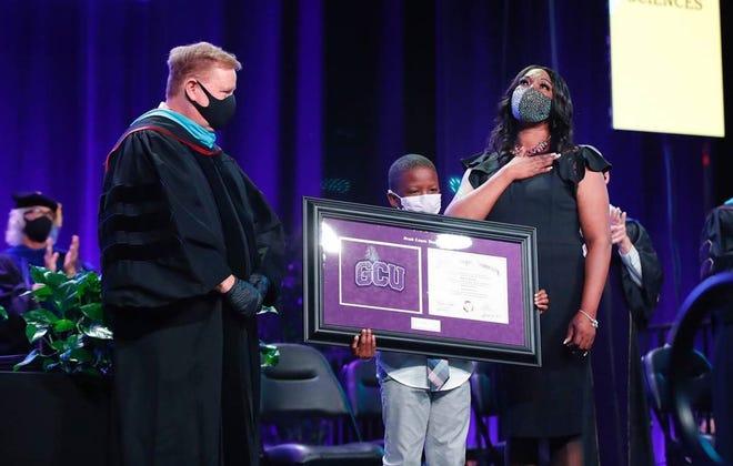 Bionca Sparrow and her grandson, E.J. Harris, accept her son Oscar Frayer's diploma during Monday's Grand Canyon University graduation ceremony. Photo by David Kadlubowsk/GCU