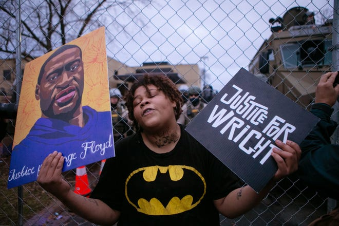 BROOKLYN CENTER, MN - APRIL 14: A demonstrator reacts along a perimeter fence guarded by police during a protest decrying the shooting death of Daunte Wright, while also holding a rendering of George Floyd, outside the Brooklyn Center Police Department, Wednesday, April 14, 2021, in Brooklyn Center, Minn. (Jason Armond / Los Angeles Times/TNS)