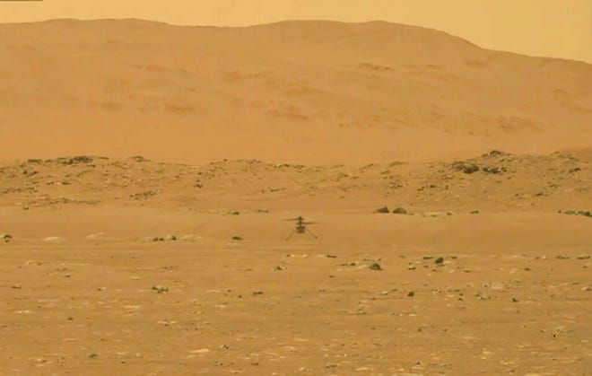 In this image from NASA, NASA's experimental Mars helicopter Ingenuity lands on the surface of Mars Monday, April 19, 2021. The little 4-pound helicopter rose from the dusty red surface into the thin Martian air Monday, achieving the first powered, controlled flight on another planet. (NASA via AP)