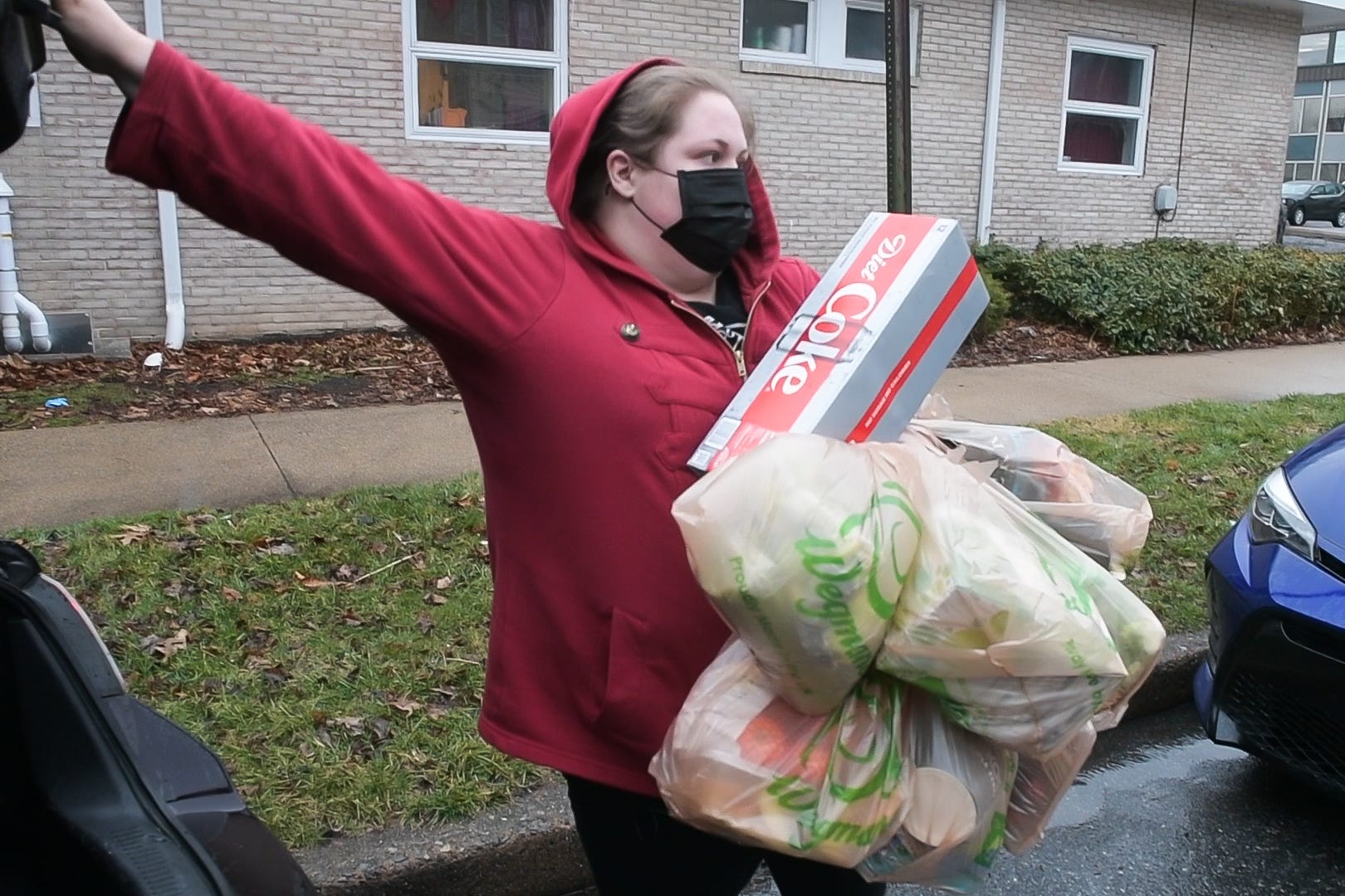 Amanda Cree closes her car trunk after loading up her arm with grocery bags while making an Instacart delivery in Harrisburg on Thursday, March 18, 2021.
