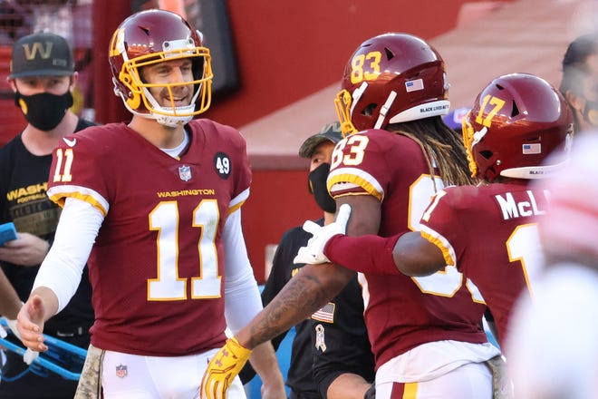 Washington Football Team quarterback Alex Smith (11) celebrates with Washington Football Team wide receiver Terry McLaurin (17) after the two connected on a touchdown pass against the New York Giants in the fourth quarter at FedEx Field.