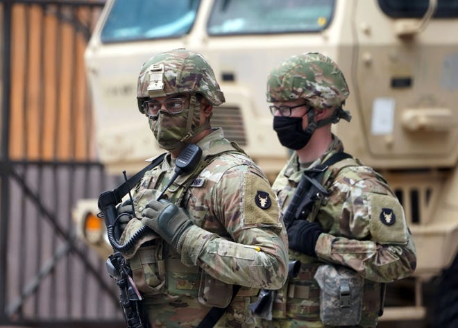 Members of the Minnesota National Guard stand at an intersection in downtown Minneapolis shortly before jurors were set to begin deliberations in the murder trial of former police officer Derek Chauvin in the death of George Floyd.
