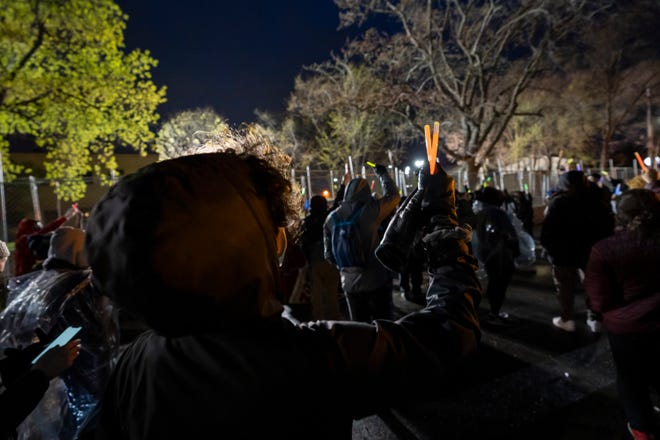 Community members hold up glow sticks during a protest outside the Brooklyn Center Police Department on April 18, 2021, after the fatal shooting of Daunte Wright.