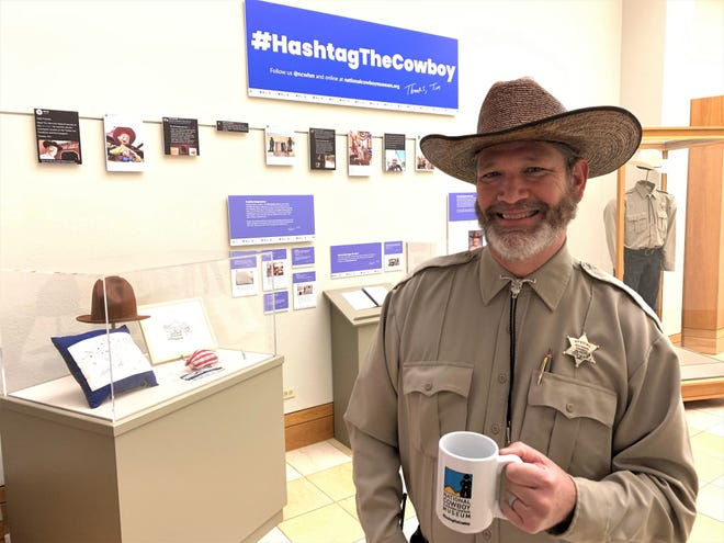 """Tim Tiller took over the the National Cowboy & Western Heritage Museum's social media during the shutdown and became an internet sensation. Here's he's pictured with his coffee mug and fan gifts at the """"#HastagTheCowboy"""" exhibit in Oklahoma City."""