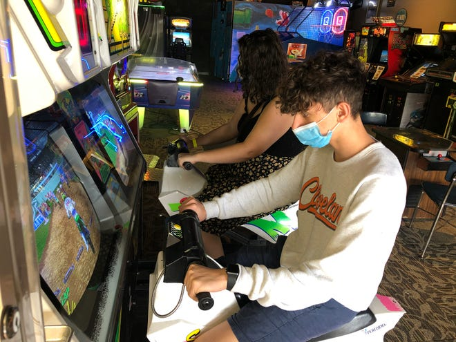 Beacon Journal writer Craig Webb's son Ethan and daughter Teagan try out a racing game at Akron's Quarter Up Bar & Arcade.