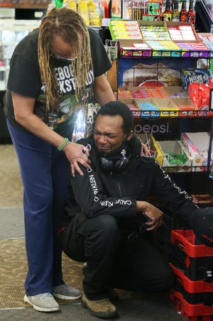 Norma Heard, owner of 2 Live Music in Akron, comforts customer Avery Norris, 25, of Akron on Tuesday after he breaks down in tears of relief after former police officer Derek Chauvin was found guilty of all three counts in the death of George Floyd in Minneapolis.
