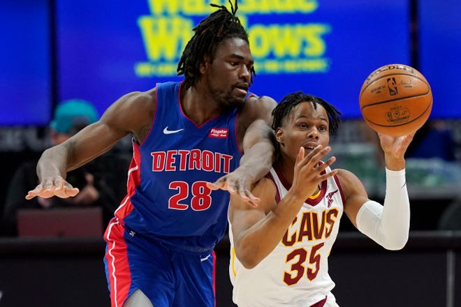 Detroit Pistons center Isaiah Stewart (28) reaches in on Cavaliers forward Isaac Okoro (35) during the Cavs' 109-105 loss Monday night in Detroit. [Carlos Osorio/Associated Press]