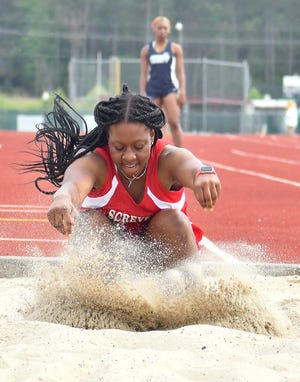 Lady Gamecock Ta'myia Tyler kicks up sand in the pit as she completes her triple jump attempt at home on April 15. Tyler took third place in the event.