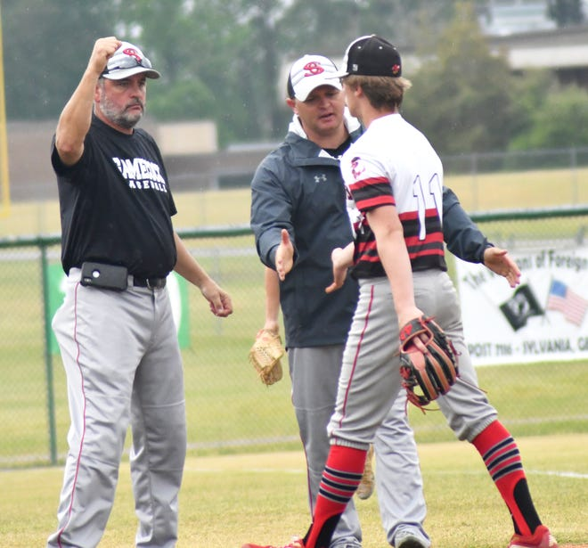 SCHS head baseball coach JR Doyle and Principal/Athletic Director Brian Scott congratulate junior pitcher Chase Hart after the Gamecock made a nice play off the mound on a short roller in the infield.