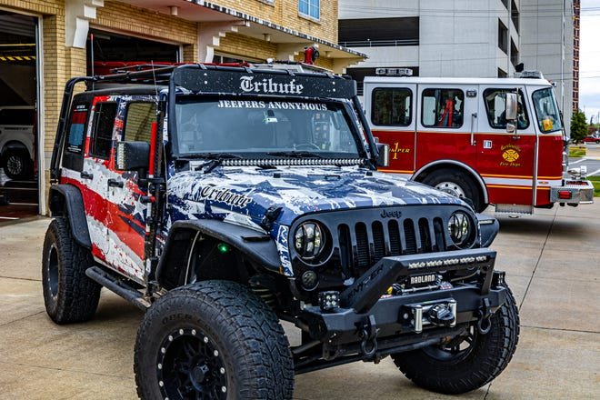 """Jon Beckloff, organizer of Project Tribute Foundation, drives the """"Tribute Jeep"""", which is decorated with lights and flags, with the names of hundreds of first responders who died in the line of duty nationwide in 2020 inscribed on the windows."""