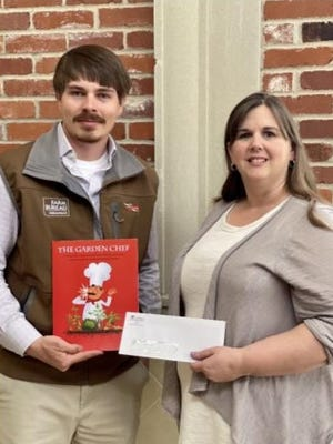 Arkansas Farm Bureau's education coordinator Brock Roberts presents Sabrina Ketter, Charleston Middle School's fifth and sixth grade science teacher, with a $500 grant. The grant will be used to modify the school's outdoor garden.
