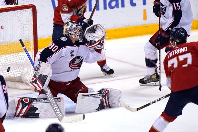 Florida Panthers center Frank Vatrano (77) scores a goal against Columbus Blue Jackets goaltender Elvis Merzlikins (90) during the first period of an NHL hockey game, Monday, April 19, 2021, in Sunrise, Fla. (AP Photo/Lynne Sladky)