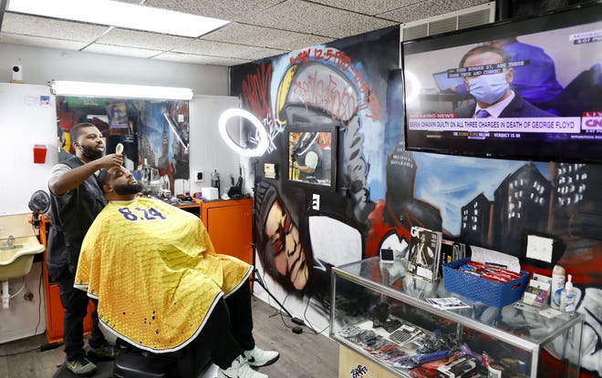 Barber Jamal Islam stops cutting the hair of Ray Woods to listen to the verdict of the Derek Chauvin trial at FresherFades Barber Studio on Mount Vernon Avenue.