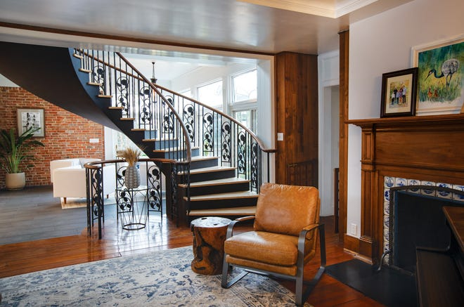 A former aqua-colored iron stairway was repainted in black as homeowners attempted to modernize the historic dwelling.