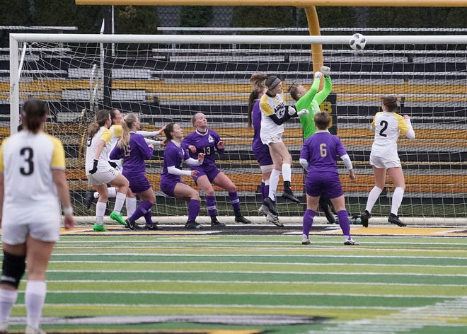 Albion College goalkeeper Romee Natschke punches the ball away during a corner kick by Adrian College during Monday's MIAA tournament game.