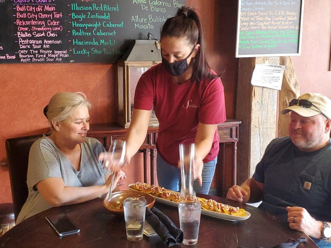 Cherie and Steven Harris are served their lunchtime order at Sophie's Cork & Ale in Lexington on Tuesday by Kristin Grorgan, who is currently the restaurant's only server available to work daytime. Sophie's Cork & Ale, like many restaurants now are struggling to hire and keep staff.