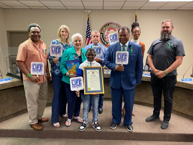 """Jarrius """"Little JJ"""" Robertson, shown at center with the proclamation, was among the special guests April 15 at Donaldsonville Mayor Leroy Sullivan's Facebook Live program. Also pictured, from left, are: Constable Jeffery Henry, Lori Steele, Peggy Guillot, Don Guillot, Mayor Sullivan, Sid Williams, and Pastor Matt Bender."""