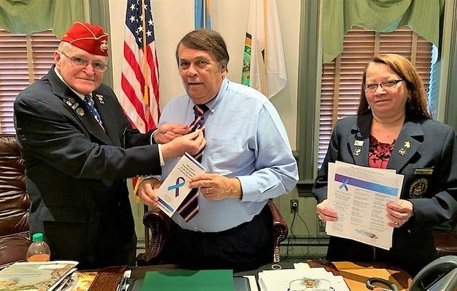 Commissioner Bill Farley presents the pin to Mayor Robin Christiansen, who holds the brochure that contains information about the program as Anna Lopez, vice chair of the Delaware Veterans Commission, looks on.