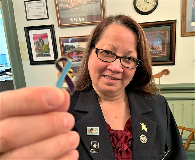Anna Lopez, vice chair of the Delaware Veterans Commission, displays the newly designed Suicide Awareness pin at Dover Mayor Robinson Christian's office.
