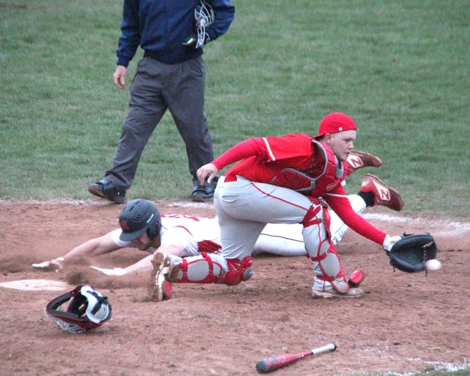 Coldwater catcher Cole Smith fields the ball during a play at the plate versus Marshall on Monday