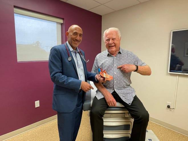 "Ascension St. Vincent's cardiologist Samer Garas (left) reunites with patient Ted Jackson, who was diagnosed with heart valve disease in 2018. Jackson returned to ""normal life"" after Garas performed a transcatheter aortic valve replacement, as shown in the heart model he is holding."