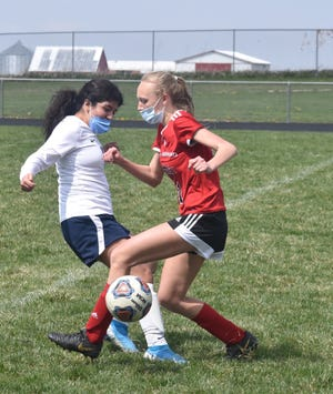 Olivia Thomsen, right, of Orion-Sherrard keeps the ball from a defender during a game with Monmouth-Roseville on Saturday, April 17, at Charger Field.