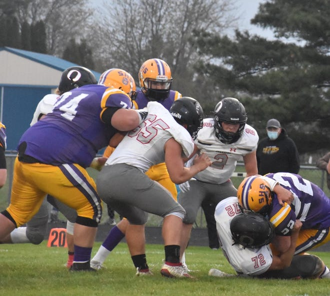 Orion's Jayson Johnson (72), far right, drags down the Sherrard runner on a third down play as the first quarter ends on Friday, April 16, on the Tiger field. Johnson kept Sherrard from getting a first down on the play, and the Tigers had to punt. Also in on the play are, standing from left, Josh Fair (65) and Coby Schultz (2)